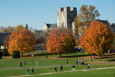 sunny view of Burruss Hall and drillfield surrounded by orange autumn leaves
