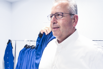 man dons a blue lab coat in prep room