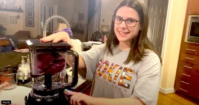 Woman stands in home kitchen with blender and smiles at camera