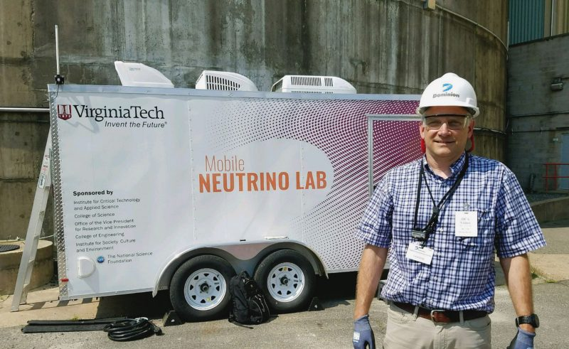 Link with hardhat in front of mobile neutrino lab trailer at North Anna power plant
