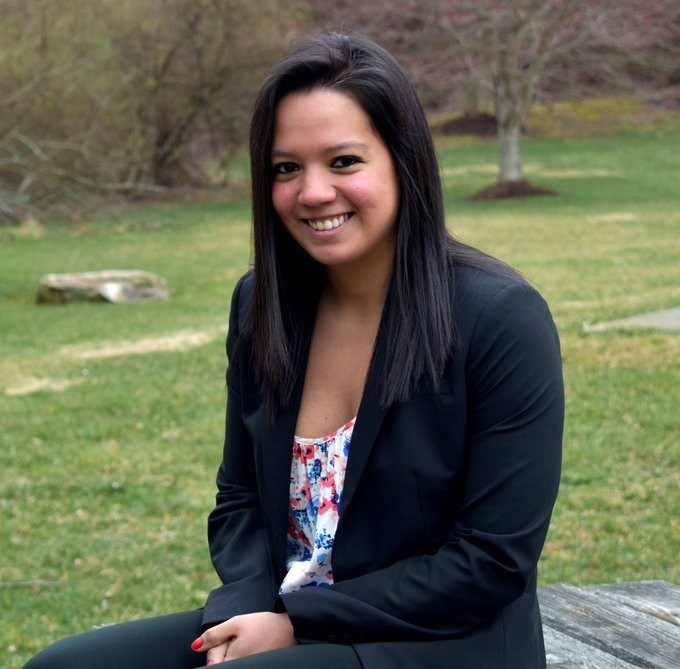 Erika Hernandez sits on picnic bench with grassy background