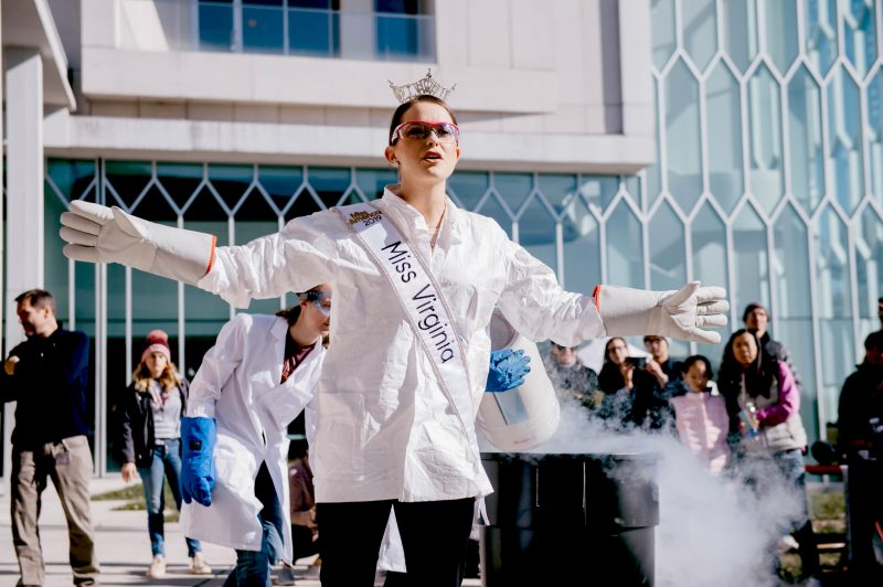 Camille performs chemistry demo outside Moss Arts Center with lab coat, Miss Virginia sash and crown and hot pink jeweled lab safety glasses